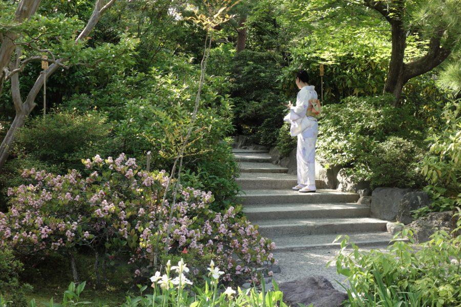 Femme en kimono montant des escaliers dans un jardin